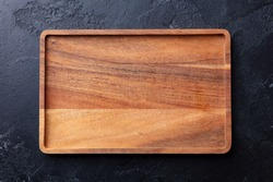 Wooden tray, cutting board. Dark background. Copy space. Top view.