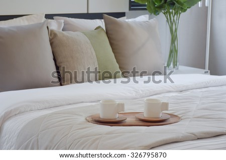 wooden tray of tea set on bed in modern bedroom interior