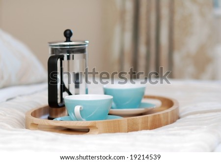 Wooden tray on the bed prepared for serving the breakfast