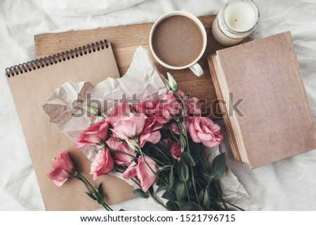 Wooden tray with coffee and spring flowers, craft paper and sketchbook. Eco home objects concept.
