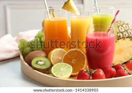 Photo of  Wooden tray with glasses of different juices and fresh fruits on table