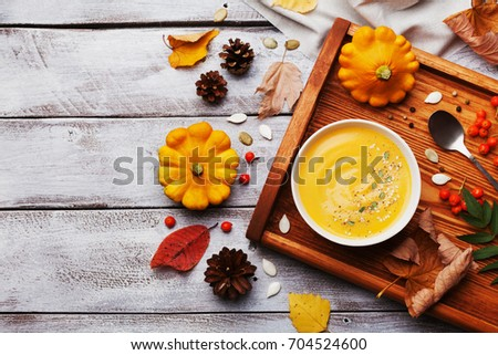 Wooden tray with hot autumn pumpkin soup decorated sesame seeds and thyme in white bowl on rustic vintage table top view. Cozy lifestyle shot for halloween menu