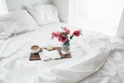Wooden tray with paper sketchbook, candle and spring flowers on clean white bedding. Good morning concept.