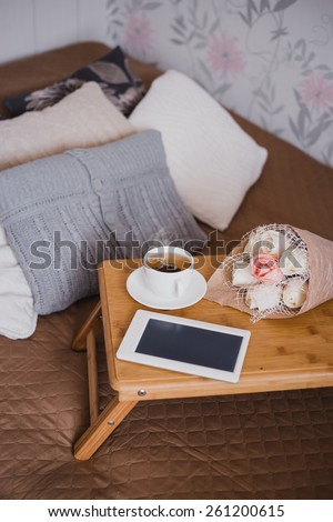 Wooden tray with tea, flowers and e-book standing on a bed with decorative pillows in a bedroom. Cozy scandinavian interior