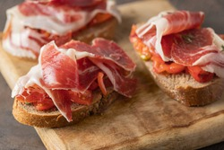 Wooden try with toasted brad slice with fresh tomatoes and cured ham. Delicious appetiser Italian prosciutto and Spanish Iberian ham snack