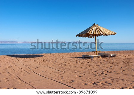 Wooden umbrella and chairs on the beach