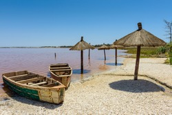 Wooden umbrellas, boat on the pink water lake in Senegal