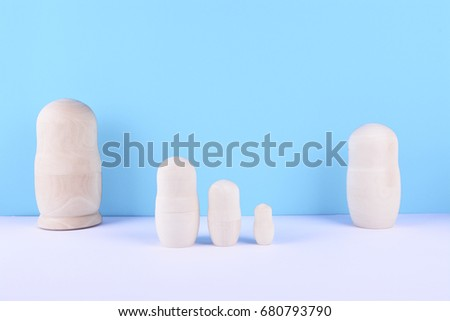 Wooden unpainted russian nested dolls (matryoshka) on blue background. Family concept. #680793790