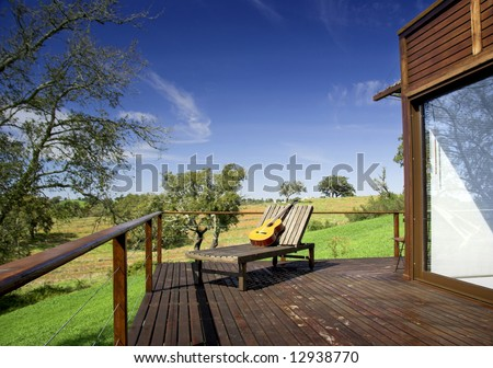 Wooden vacation house with a nice balcony and a long chair with a guitar on top