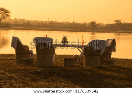 Wooden vintage Old table and old chairs near the lake in the morning #1176539542