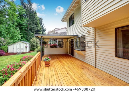 Wooden walkout deck. Well kept garden with bushes and flowers. Northwest, USA #469388720