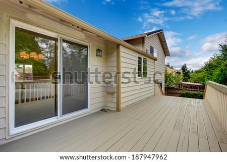 Wooden walkout deck with glass slide doors. #187947962