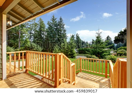 Wooden walkout deck with patio area overlooking backyard #459839017