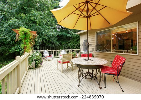 Wooden walkout deck with patio table, umbrella and chairs #224835070