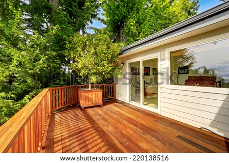 Wooden walkout deck with railings and decorated with tree. #220138516