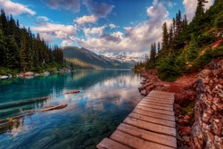 Wooden walkway along clear mountain lake and evergreen trees