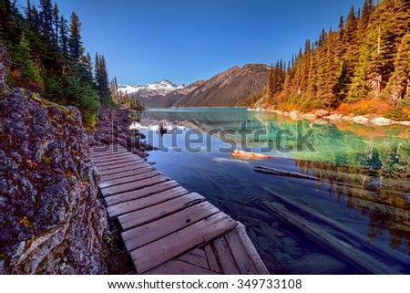 Wooden walkway along the glacial lake, with pine trees and mountains