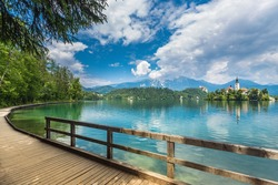 Wooden walkway around the lake Bled and the Catholic church of St. Mary situated on an island on Bled lake with mountains and villages on the background