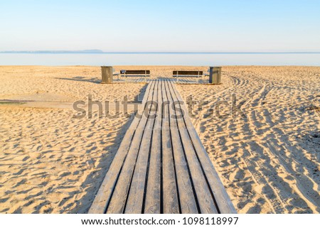 Wooden walkway at a beach, with two empty benches and trash bins on the sides. Windless sea under the horizon on a sunny morning before the bathers arrive. Angelholm in Sweden. Stock photo ©