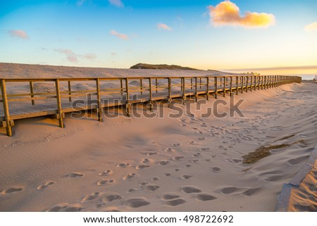 wooden walkway covered in sand...