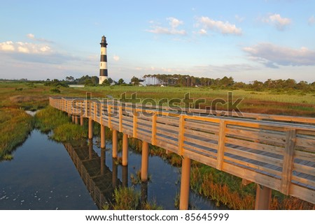 Wooden walkway from a viewpoint in the marsh leads to the Bodie Island lighthouse on the outer banks of North Carolina against a blue sky and white clouds