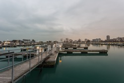 Wooden walkway leading to empty boat docks with cloudy sky in Chicago