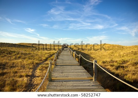 Wooden walkway over the sand dunes to the beach - stock photo