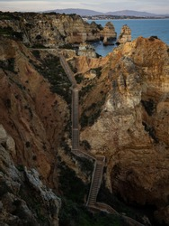 Wooden walkway stairs path staircase sunset panorama view of Ponta da Piedade beach cape ocean sea stack rock formations in Lagos Algarve, Portugal Europe