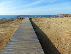 Wooden walkway to the cliffs in Carrapateira, Portugal. Pontal de Carrapateira trail in Algarve. Vicentine coast.
