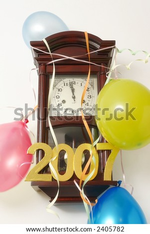 Wooden wall clock decorated with streamers and balloons indicating almost 12 p.m. hour on New Year's Eve