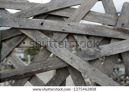 Wooden Wall made up of boards arranged in a crisscrossing pattern