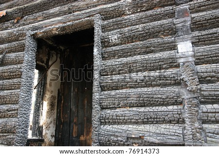 Wooden wall of the burned down house.