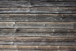 Wooden wall with gray and brown bars. Texture old wood is used in a design, furniture making and construction. Wood is trendy. Dry wood. Wood is a common material in a construction. Old bars with crac