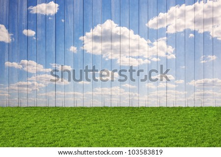 wooden wall with painted sky and floor from the green grass.