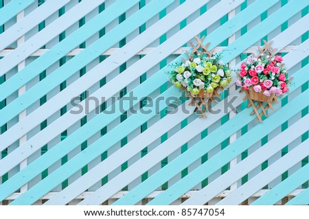 Wooden walls are white with a green switch. Hanging flowers.