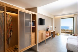 Wooden wardrobe cabinet furniture in white in modern minimalistic style interior of double hotel room with open sea view terrace