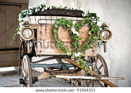 Wooden wedding carriage with a wreath formed like a heart