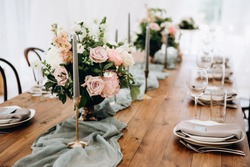 Wooden wedding table decoration with flowers and candles