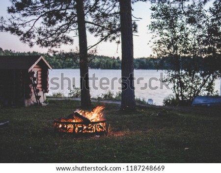 Wooden weekend cabin on a lake in summer with bon fire, evening picture