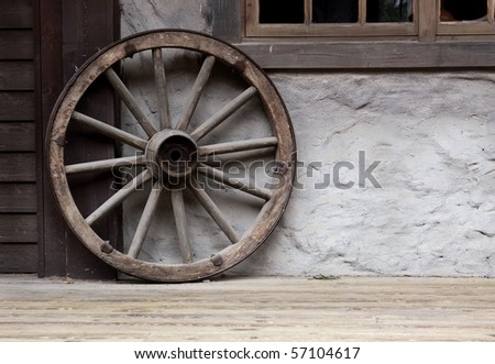 Wooden wheel leaning against a wall
