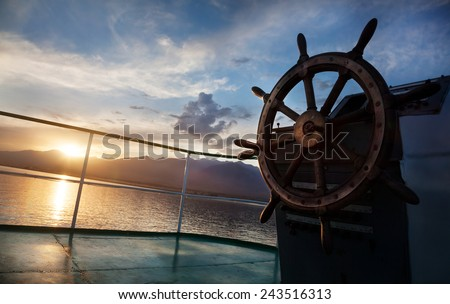 Wooden wheel on the ship at sunset on Issyk Kul lake