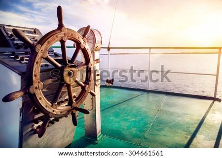 Wooden wheel on the ship at sunset on Issyk Kul lake