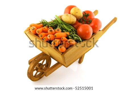 wooden wheelbarrow full with fresh vegetables isolated over white