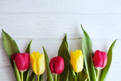 Wooden white background and red and yellow tulips. Conception holiday, March 8, Mother's Day.
