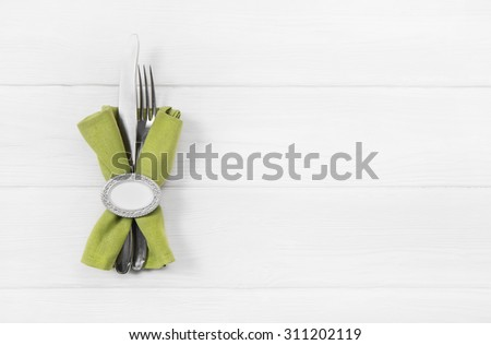 Wooden white background for a menu card with cutlery in red white checked colors for restaurants and gastronomy placards.