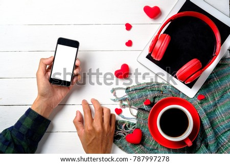 Wooden white background with hand holding blank screen smartphone, red hearts,tablet,head phone and red cup of coffee. The concept of Valentine Day,Wedding day. #787997278