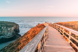 Wooden white bright color walking path with hand rails nature with fields forest and ocean sunrise sunset orange sun light and sky Romantic mystical in beach of cathedrals as catedrais Spain, Galicia