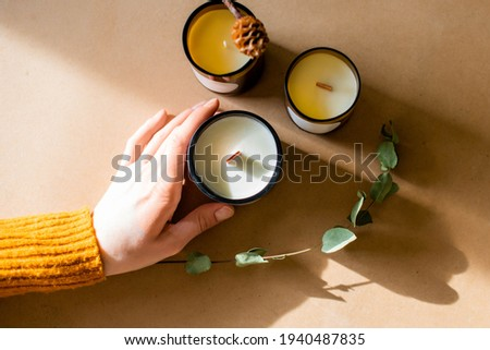 wooden wick candles. Handmade candle from paraffin and soy wax in glass with leaf on craft background. Let flay. Candle making. Top view. Womans hands holding the candles