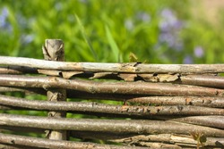 Wooden wicker fence of branches made of twigs.