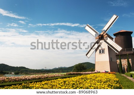 Wooden windmill on blue sky background